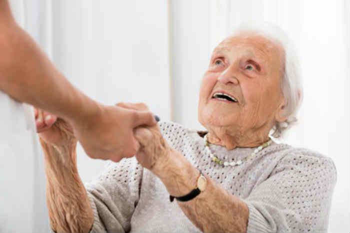 infermiere aiuta anziana ad alzarsi